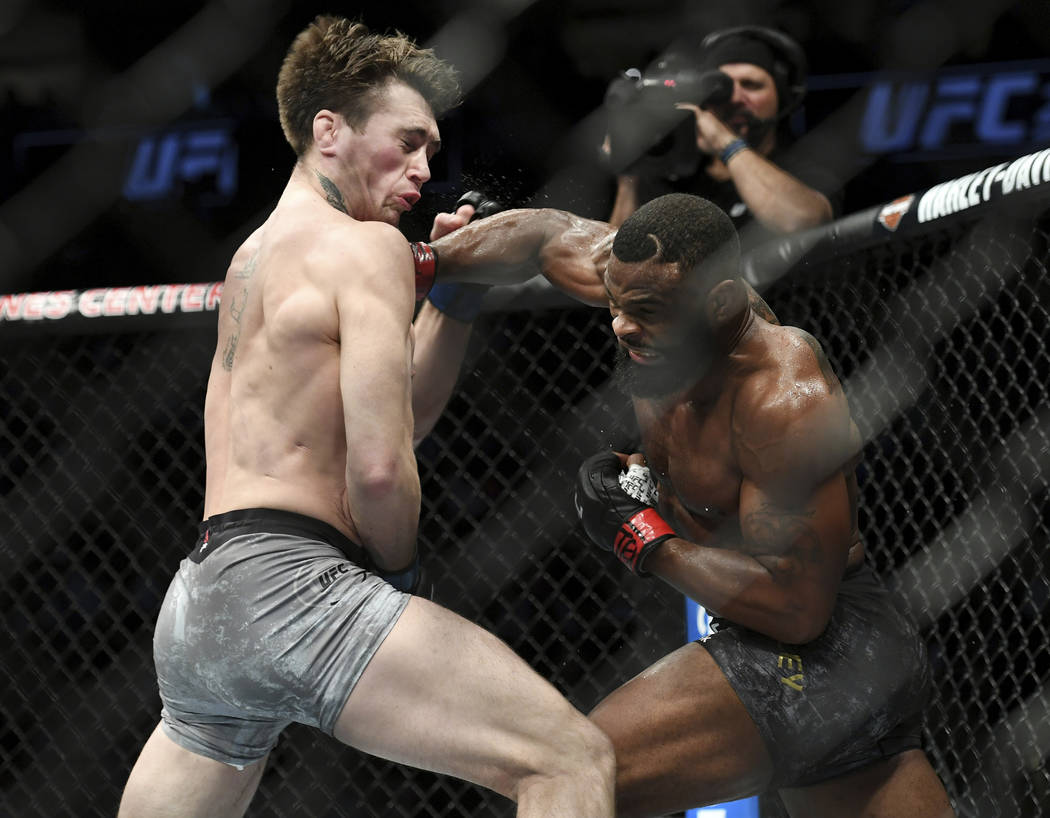 Tyron Woodley, right, punches Darren Till during their welterweight title mixed martial arts bout at UFC 228 on Saturday, Sept. 8, 2018, in Dallas. Woodley won by submission. (AP Photo/Jeffrey McW ...