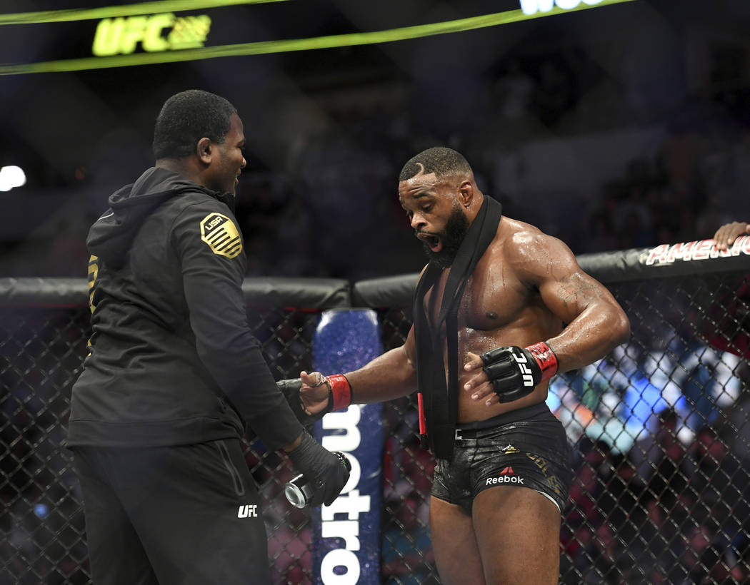 Tyron Woodley, right, reacts after defeating Darren Till by submission in their welterweight title mixed martial arts bout at UFC 228 on Saturday, Sept. 8, 2018, in Dallas. (AP Photo/Jeffrey McWho ...