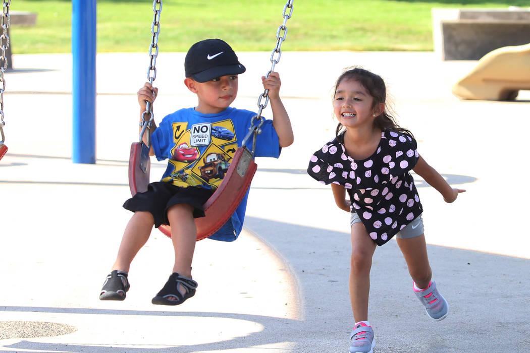 Calia Lopez, 4, pushes her brother Osiris, 2, both of Las Vegas, on a swing as they play at Sunset Park on Tuesday, July 17, 2018, in Las Vegas. Bizuayehu Tesfaye/Las Vegas Review-Journal @bizutesfaye
