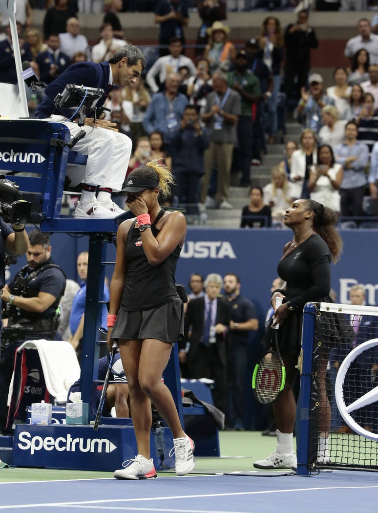 Naomi Osaka, of Japan, reacts as Serena Williams talks with chair umpire Carlos Ramos after Osaka defeated Williams in the women's final of the U.S. Open tennis tournament, Saturday, Sept. 8, 2018 ...