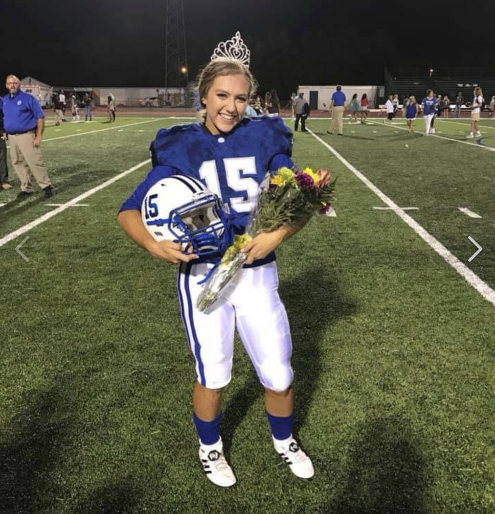 In this Friday, Sept. 7, 2018 photo provided by the Ocean Springs School District, Ocean Springs High School's 2018 Homecoming Queen Kaylee Foster holds her football helmet while wearing a ...