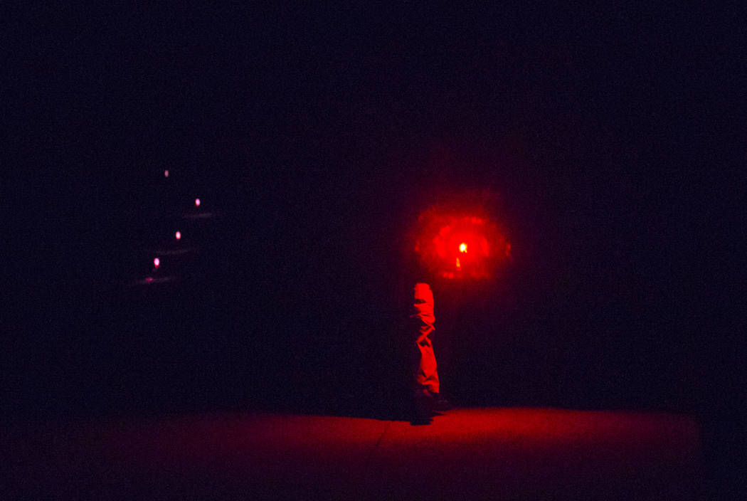 An attendee walks with a red light, used by astronomers to minimize the visual impact to the eye while stargazing, during the final day of the annual astronomy festival at Great Basin National Par ...