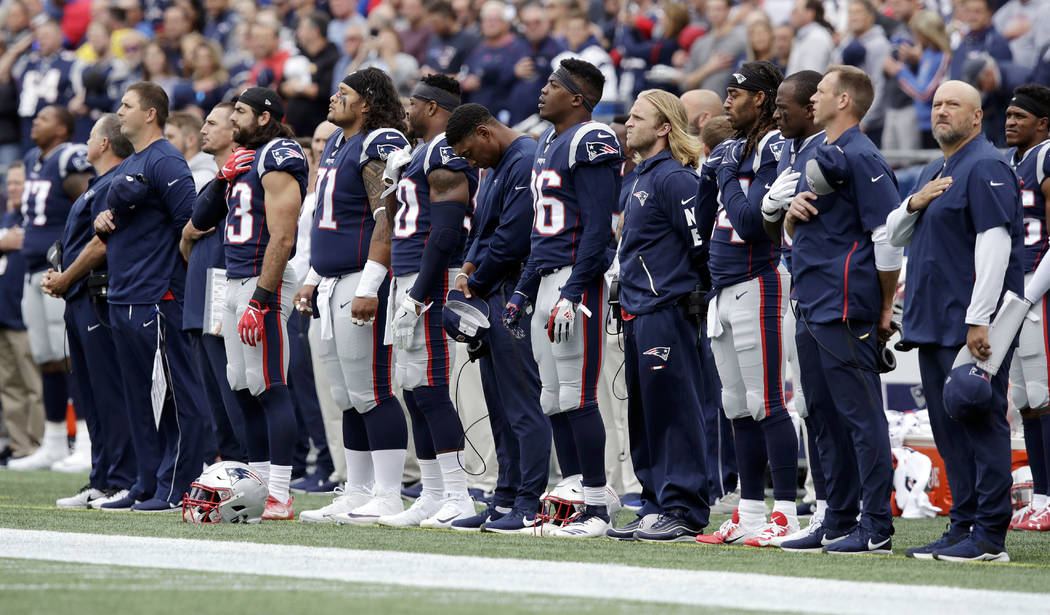 New England Patriots players stand during the national anthem before an NFL football game against the Houston Texans, Sunday, Sept. 9, 2018, in Foxborough, Mass. (AP Photo/Charles Krupa)