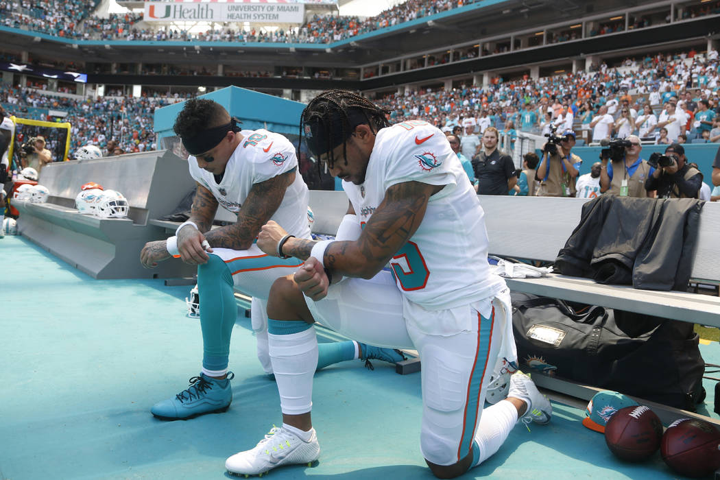 Miami Dolphins wide receiver Kenny Stills (10) and Miami Dolphins wide receiver Albert Wilson (15) kneel during the national anthem before an NFL football game against the Tennessee Titans, Sunday ...
