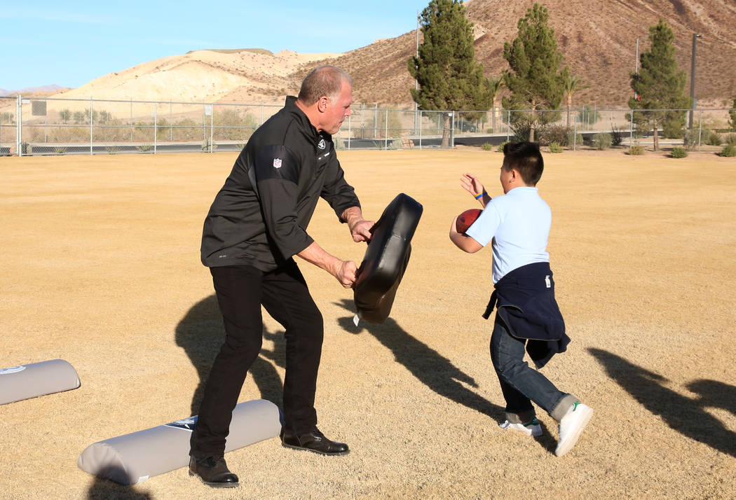 Former Raiders linebacker Linden King tries to block Ethan Miranda, 11, during the Raiders NFL Play 60 challenges event at Josh Stevens Elementary School on Tuesday, Nov. 28, 2017, in Henderson. T ...