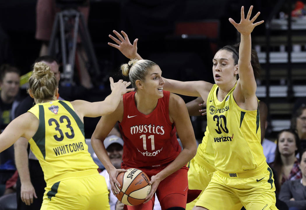 Washington Mystics' Elena Delle Donne (11) looks for room to pass as Seattle Storm's Sami Whitcomb (33) and Breanna Stewart (30) defend in the first half of Game 2 of the WNBA basketball finals Su ...