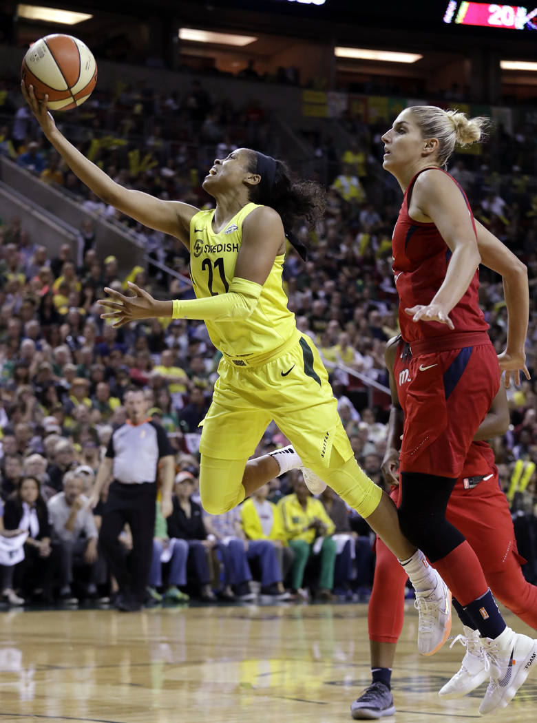 Seattle Storm's Jordin Canada (21) drives past Washington Mystics' Elena Delle Donne in the first half of Game 2 of the WNBA basketball finals Sunday, Sept. 9, 2018, in Seattle. (AP Photo/Elaine T ...