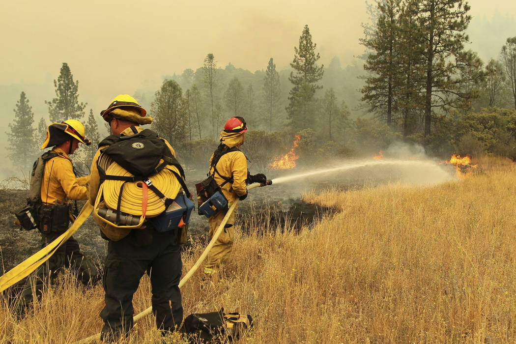 Firefighters from Yocha Dehe Fire Department work together to put out a grass fire along I-5 at Earl Sholes Memorial Bridge near Shasta-Trinity National Forest, Calif., on Sept. 7. (Hung T. Vu/The ...