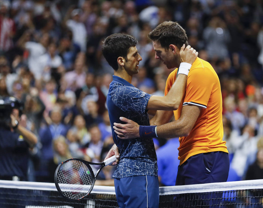 Novak Djokovic, of Serbia, left, talks with Juan Martin del Potro, of Argentina, after Djokovic defeated del Potro in the men's final of the U.S. Open tennis tournament, Sunday, Sept. 9, 2018, in ...