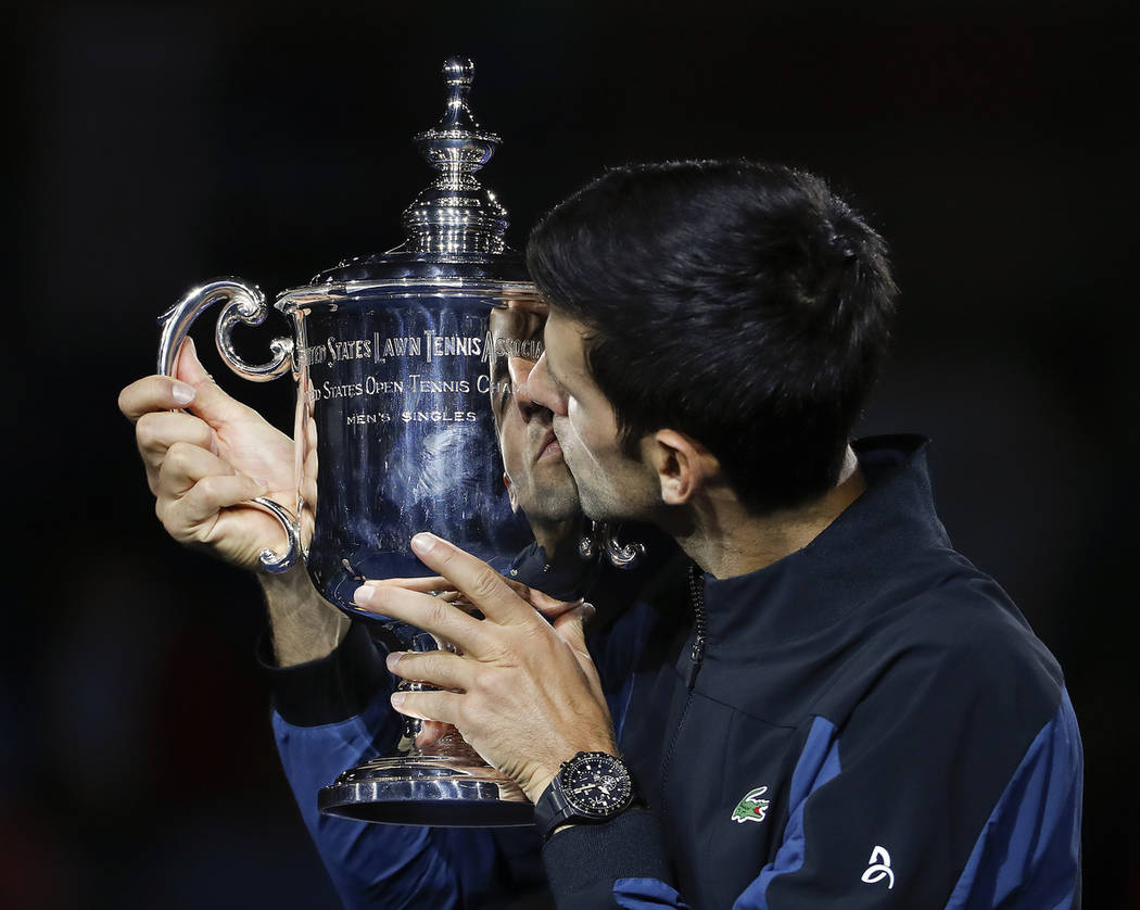 Novak Djokovic, of Serbia, kisses the trophy after defeating Juan Martin del Potro, of Argentina, during the men's final of the U.S. Open tennis tournament, Sunday, Sept. 9, 2018, in New York. (AP ...