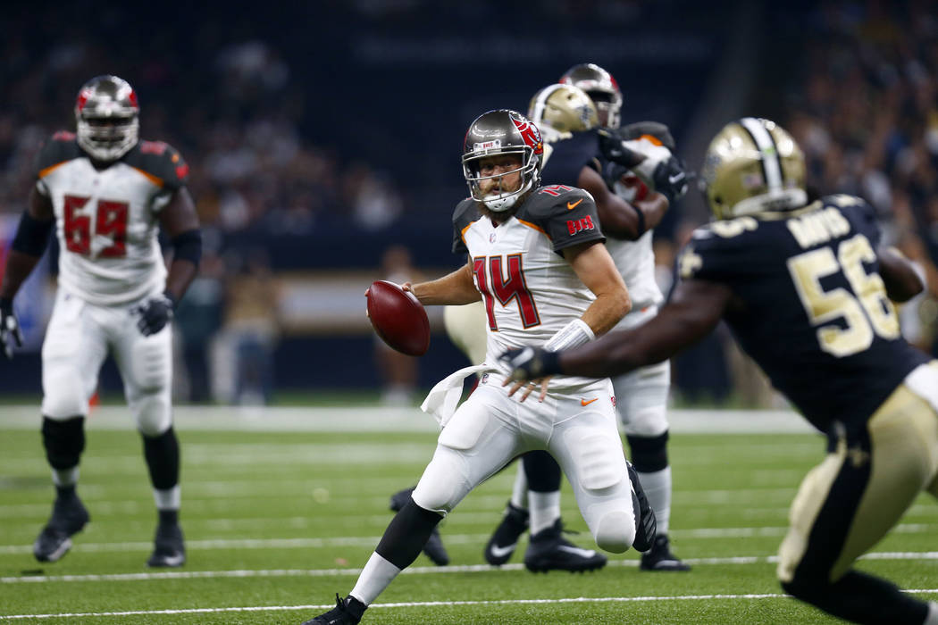 Tampa Bay Buccaneers quarterback Ryan Fitzpatrick (14) scrambles as New Orleans Saints linebacker Demario Davis (56) pursues in the first half of an NFL football game in New Orleans, Sunday, Sept. ...