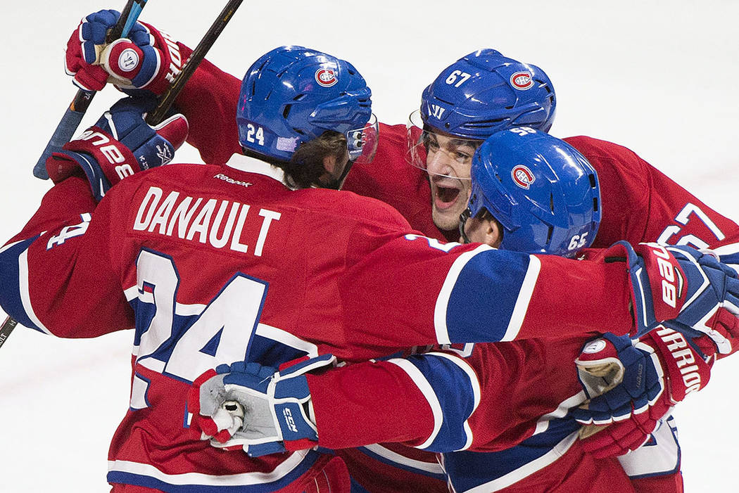 Montreal Canadiens' Phillip Danault (24) celebrates with teammates Max Pacioretty (67) and Andrew Shaw (65) after scoring against the Detroit Red Wings during the first period of an NHL hockey gam ...