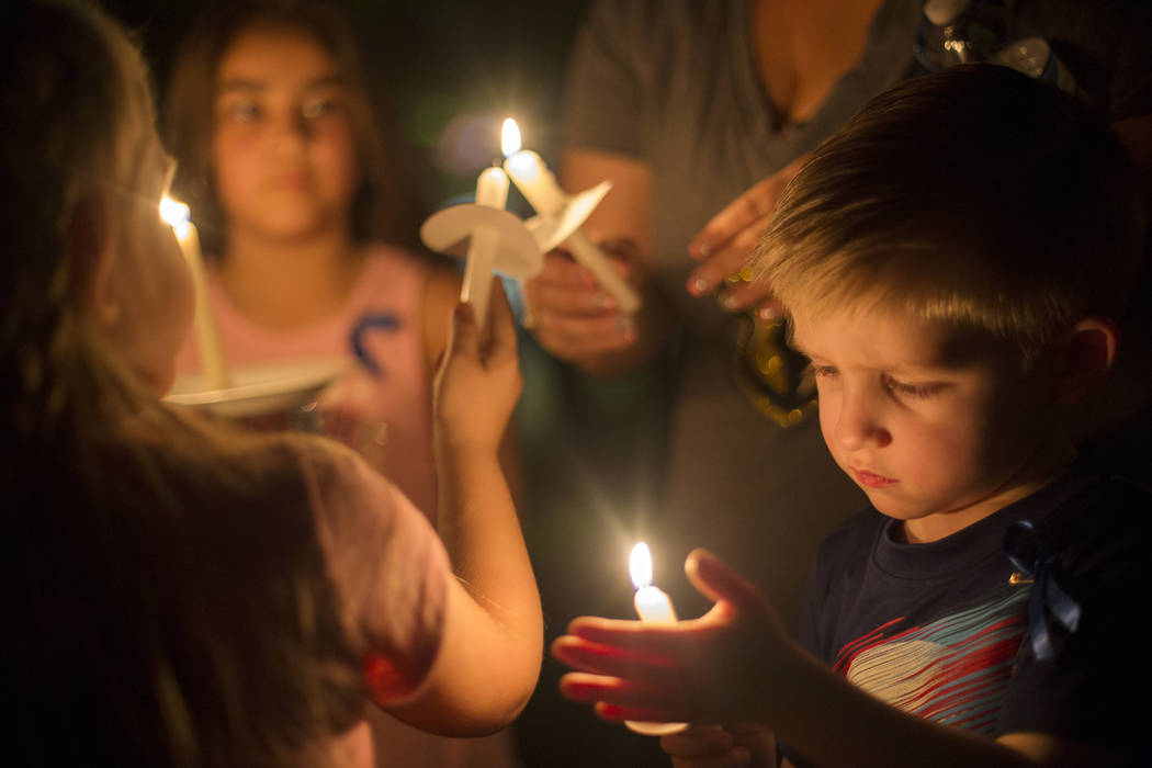 Jaxson Smith, 4, holds a candle at a vigil for 8-year-old Levi Echenique, at Paradise Park in Las Vegas, Sunday, Sept. 9, 2018. Echenique was killed in a car crash on Aug. 31. His parents Breijet ...