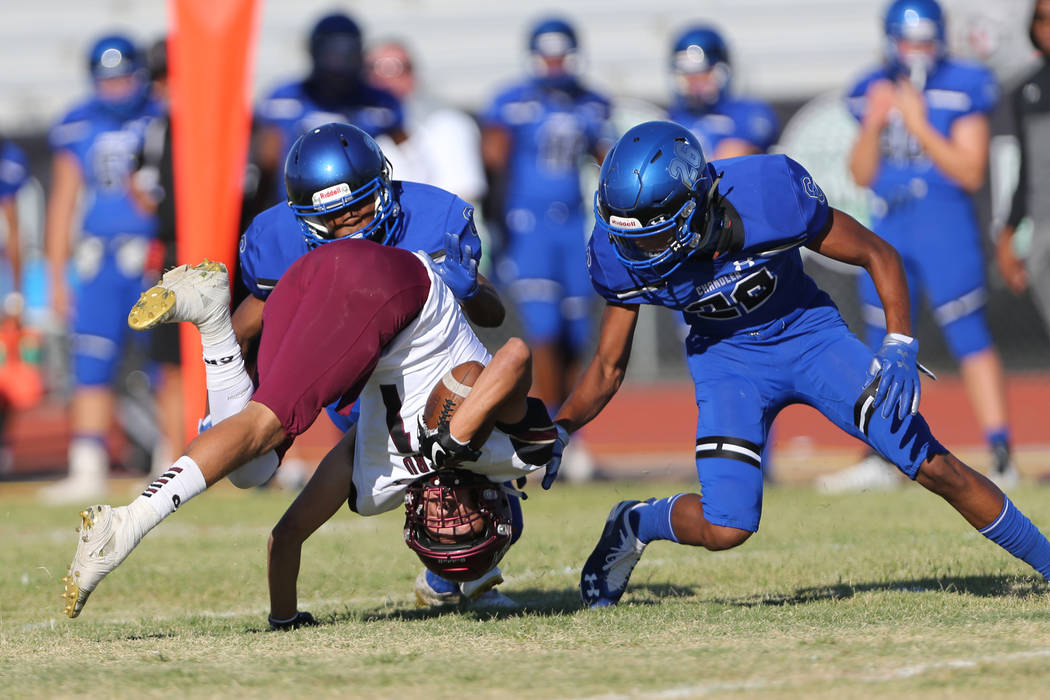 Faith Lutheran's Noah Vernon (1) is tackled by Kiondre Taylor (20), left, and Andrew Kirk (26) after a catch during the first quarter of a football game at Liberty High School in Henderson, Saturd ...