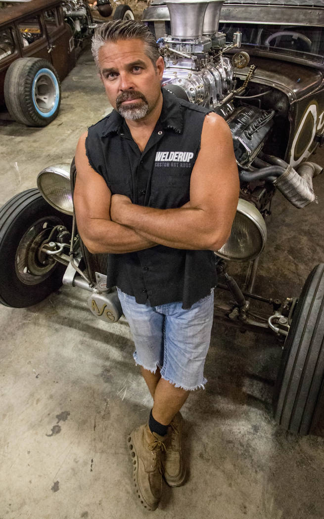 Steve Darnell leaning against a car in the shop. (Discovery Channel)