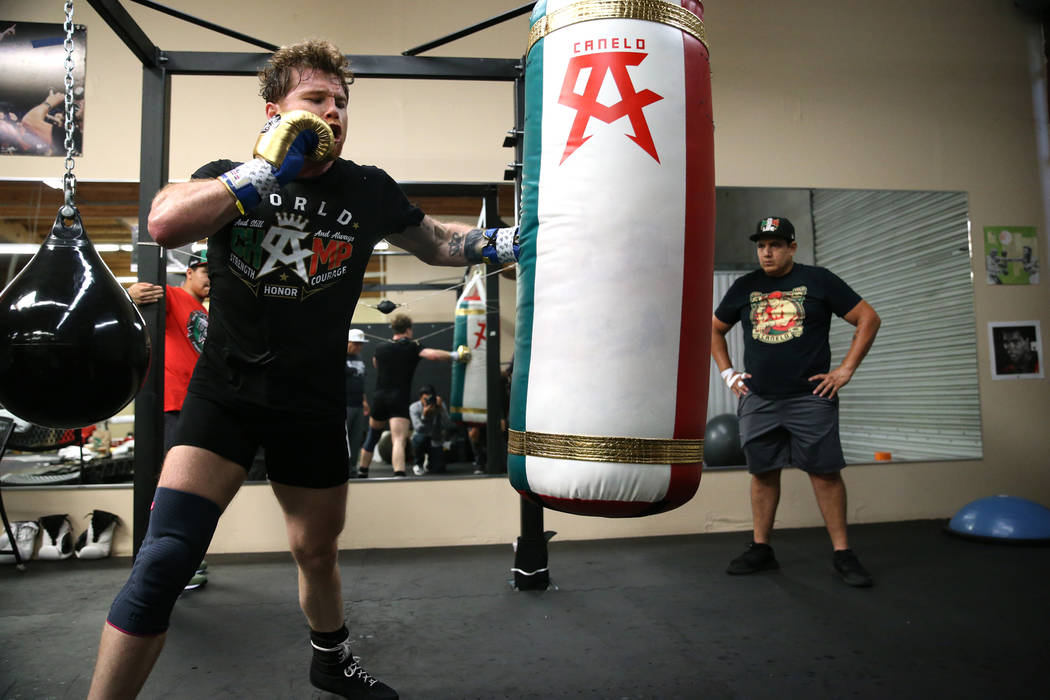 """Saul """"Canelo"""" Alvarez, left, hits the bag as his trainer Eddy Reynoso looks on during a workout at his gym in San Diego, Calif., Friday, July 27, 2018. Erik Verduzco Las Vegas Review-Jou ..."""
