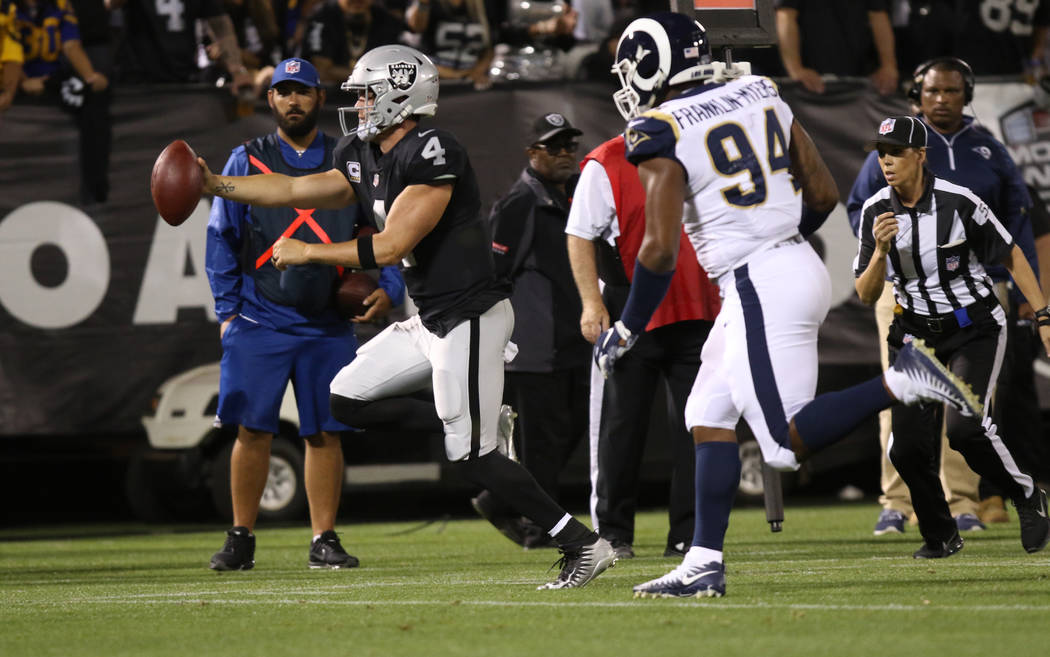 Oakland Raiders quarterback Derek Carr (4) runs with the football as Los Angeles Rams defensive end John Franklin-Myers pursues him during the first half of their NFL game in Oakland, Calif., Mond ...