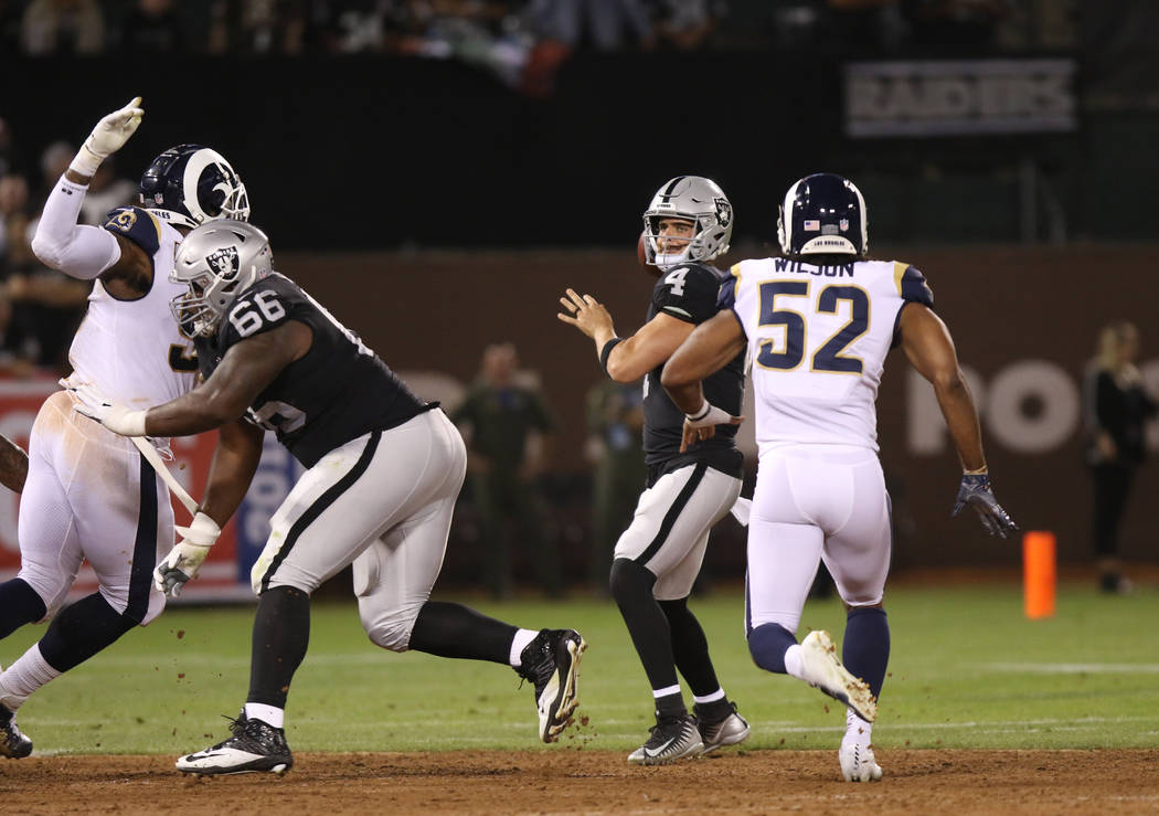 Oakland Raiders quarterback Derek Carr (4) prepares to throw the football under pressure from Los Angeles Rams linebacker Ramik Wilson (52) during the first half of their NFL game at the Oakland-A ...