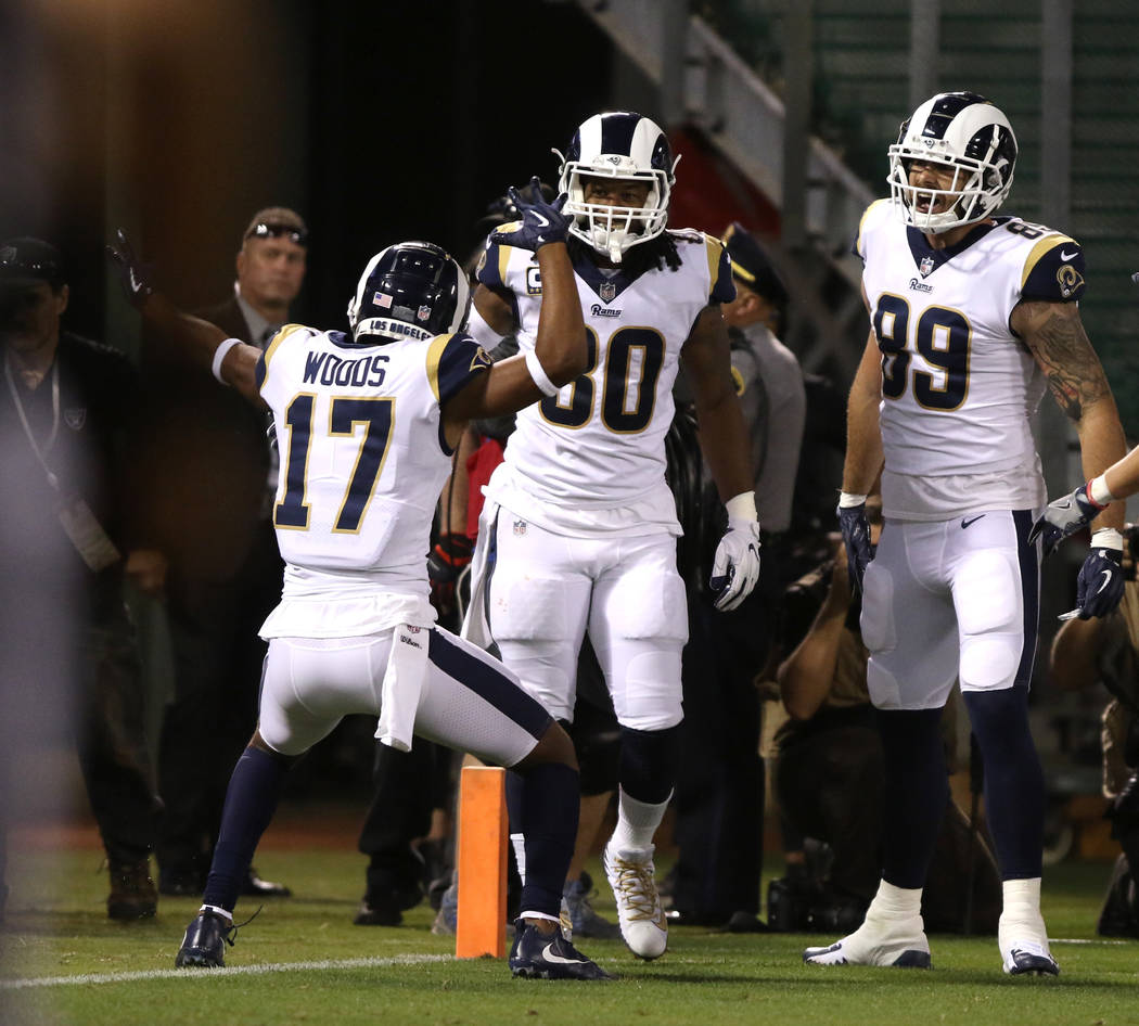 Los Angeles Rams running back Todd Gurley (30) scores a touchdown as wide receiver Robert Woods (17) and tight end Tyler Higbee (89) come to celebrate with him during the first half of their NFL g ...