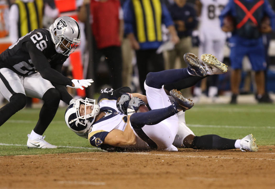 Los Angeles Rams wide receiver Cooper Kupp (18) holds on to the fotball after a catch as Oakland Raiders defensive back Leon Hall (29) looks on during the first half of their NFL game in Oakland, ...