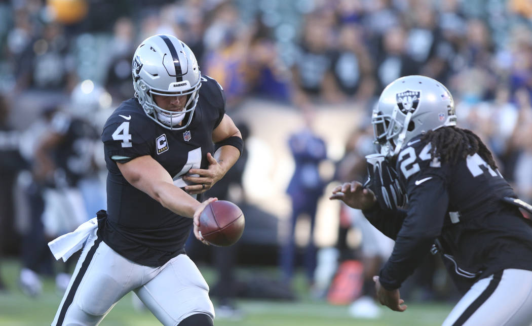 Oakland Raiders quarterback Derek Carr (4) and running back Marshawn Lynch (24) run through drills at warm ups prior to their NFL game against the Los Angeles Rams in Oakland, Calif., Monday, Sept ...