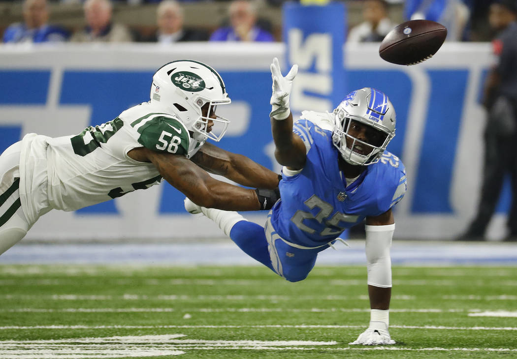 Detroit Lions running back Theo Riddick (25) reaches for the ball as New York Jets linebacker Kevin Pierre-Louis (56) defends in the first half of an NFL football game in Detroit, Monday, Sept. 10 ...