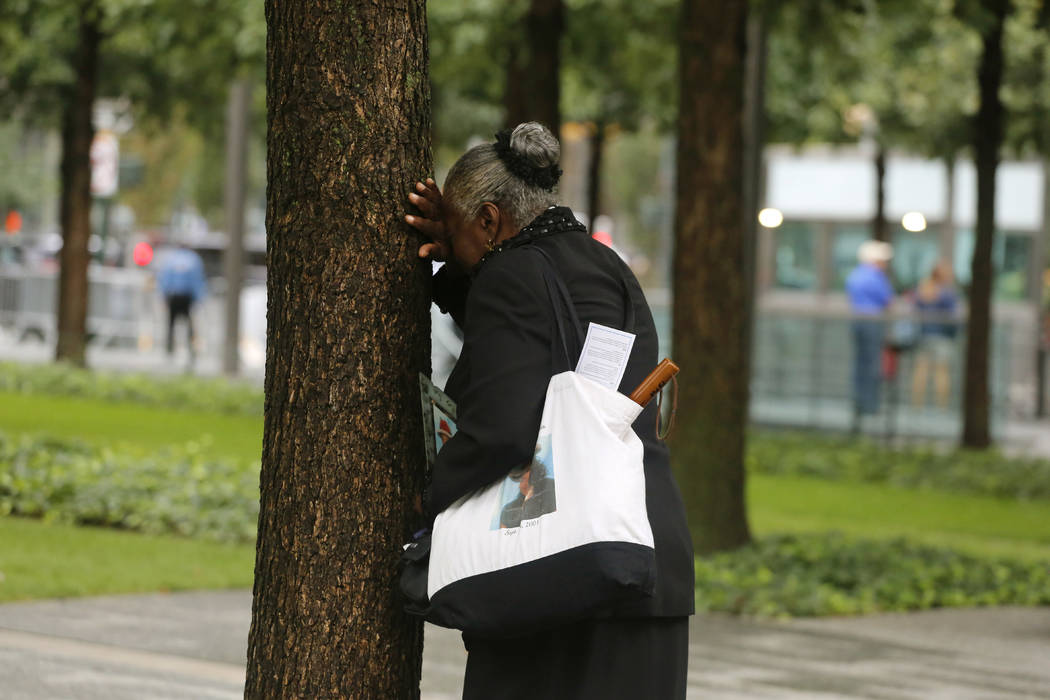 A woman weeps by herself as she leans against a tree during a ceremony marking the 17th anniversary of the terrorist attacks on the United States. Tuesday, Sept. 11, 2018, at the World Trade Cente ...