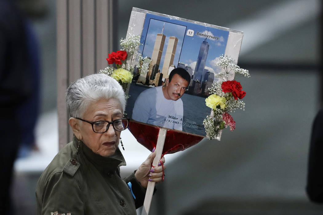 A woman arrives with a sign bearing photo memories for Wilder Gomez at the 17th anniversary of the terrorist attacks on the United States, Tuesday, Sept. 11, 2018, in New York. Gomez, from Colombi ...