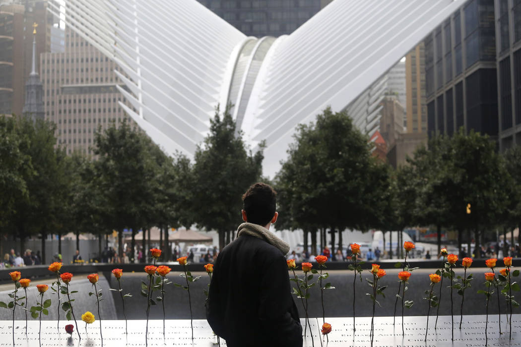 A man looks at the North Pool at the World Trade Center during a ceremony marking the 17th anniversary of the terrorist attacks on the United States. Tuesday, Sept. 11, 2018, in New York. In the b ...