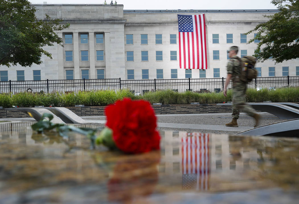 A member of the military walks the grounds of the National 9/11 Pentagon Memorial before the start of the September 11th Pentagon Memorial Observance at the Pentagon on the 17th anniversary of the ...