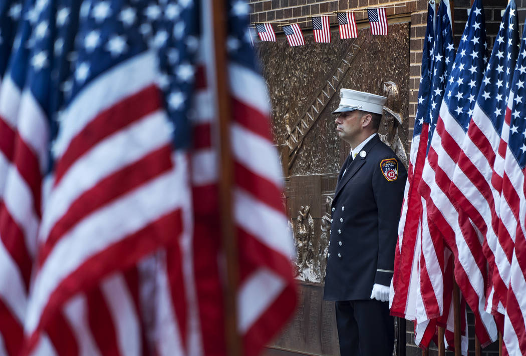 A New York City firefighter stands at attention by a memorial at the side of a firehouse adjacent to One World Trade Center and the 9/11 Memorial site during ceremonies on the anniversary of 9/11 ...