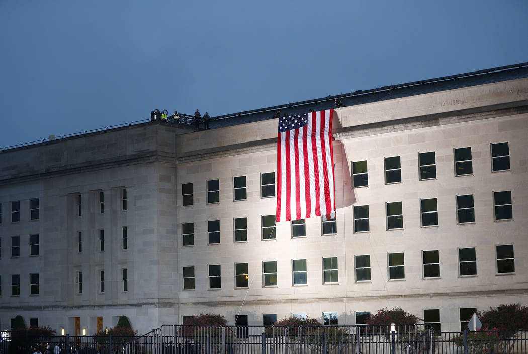 A U.S. flag is unfurled at sunrise on Tuesday, Sept. 11, 2018, at the Pentagon on the 17th anniversary of the Sept. 11, 2001, terrorist attacks. (Pablo Martinez Monsivais/AP)