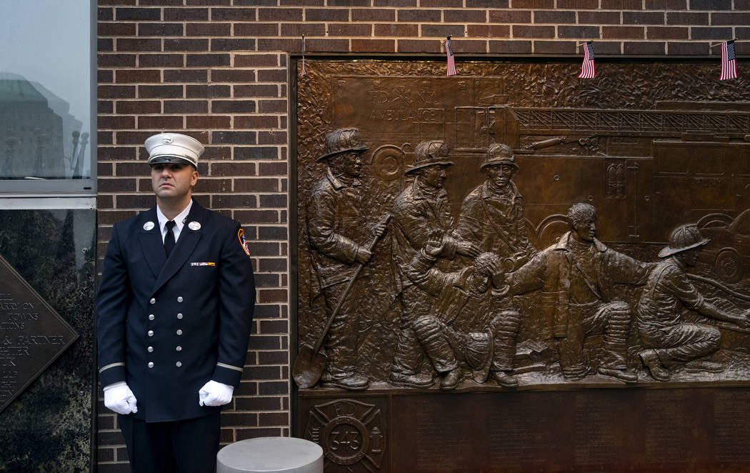 A New York City firefighter stands at attention in front of a memorial on the side of a firehouse adjacent to One World Trade Center and the 9/11 Memorial site during ceremonies on the anniversary ...