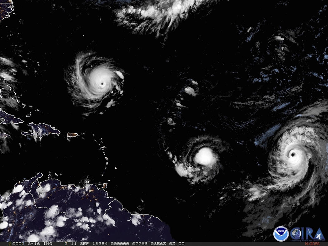 This image provided by NOAA shows Hurricane Florence, third from right, on Tuesday, Sept. 11, 2018, as it threatens the U.S. East Coast. At right is Hurricane Helene, and second from right is Trop ...