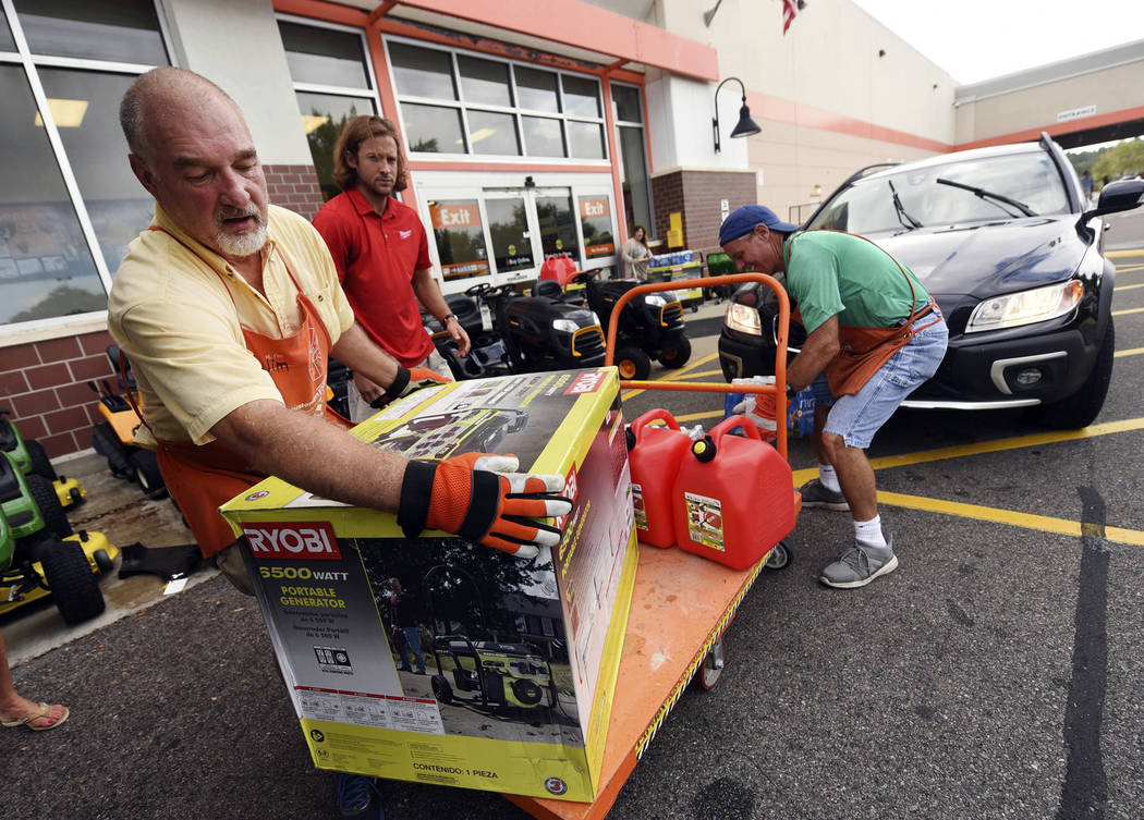 Jim Craig, David Burke and Chris Rayner load generators as people buy supplies at The Home Depot on Monday, Sept. 10, 2018, in Wilmington, N.C. Hurricane Florence rapidly strengthened into a poten ...