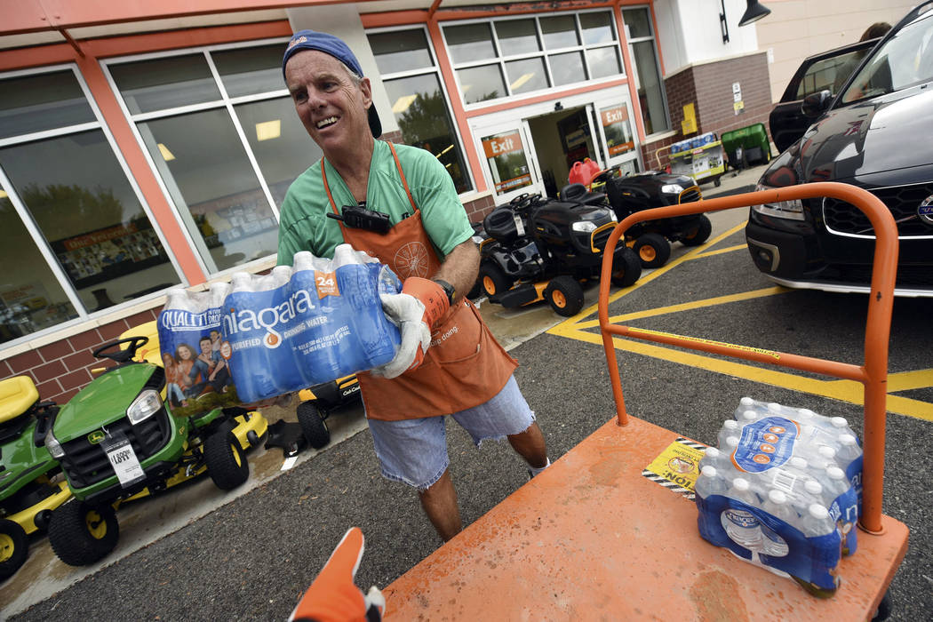 Chris Rayner helps customers load their cars as they buy supplies at The Home Depot on Monday, Sept. 10, 2018, in Wilmington, N.C. Hurricane Florence rapidly strengthened into a potentially catast ...