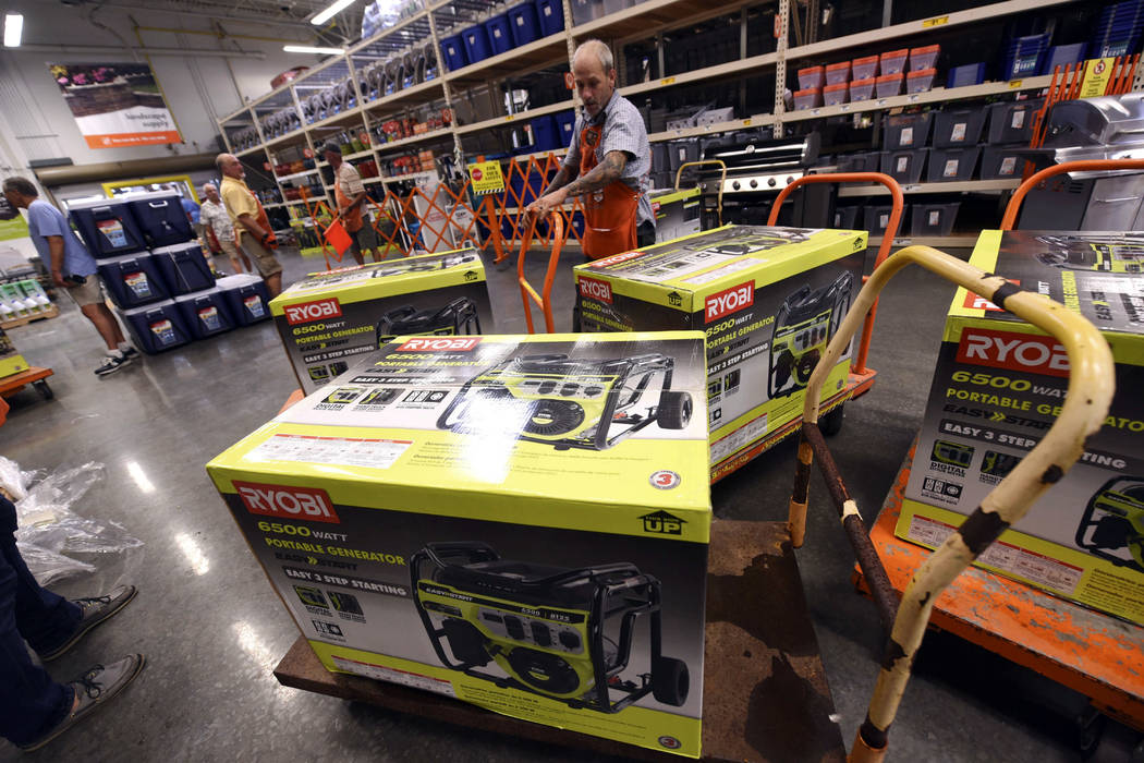 Brian Franklin prepares more generators for sale as people buy supplies at The Home Depot on Monday, Sept. 10, 2018, in Wilmington, N.C. Hurricane Florence rapidly strengthened into a potentially ...