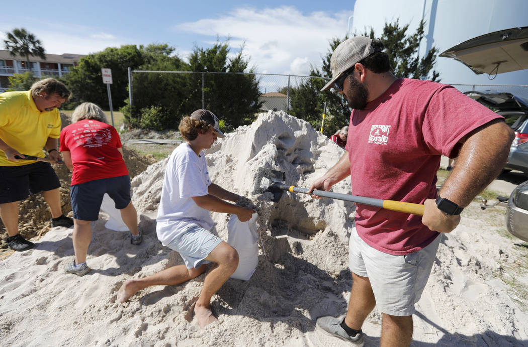 Walker Townsend, at right, from the Isle of Palms, S.C., fills a sand bag while Dalton Trout, in center, holds the bag at the Isle of Palms municipal lot where the city was giving away free sand i ...