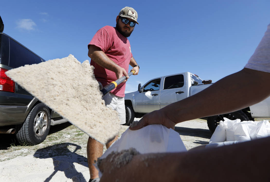 Walker Townsend, at left, from the Isle of Palms, S.C., fills a sand bag while Dalton Trout, at right, holds the bag at the Isle of Palms municipal lot where the city was giving away free sand in ...