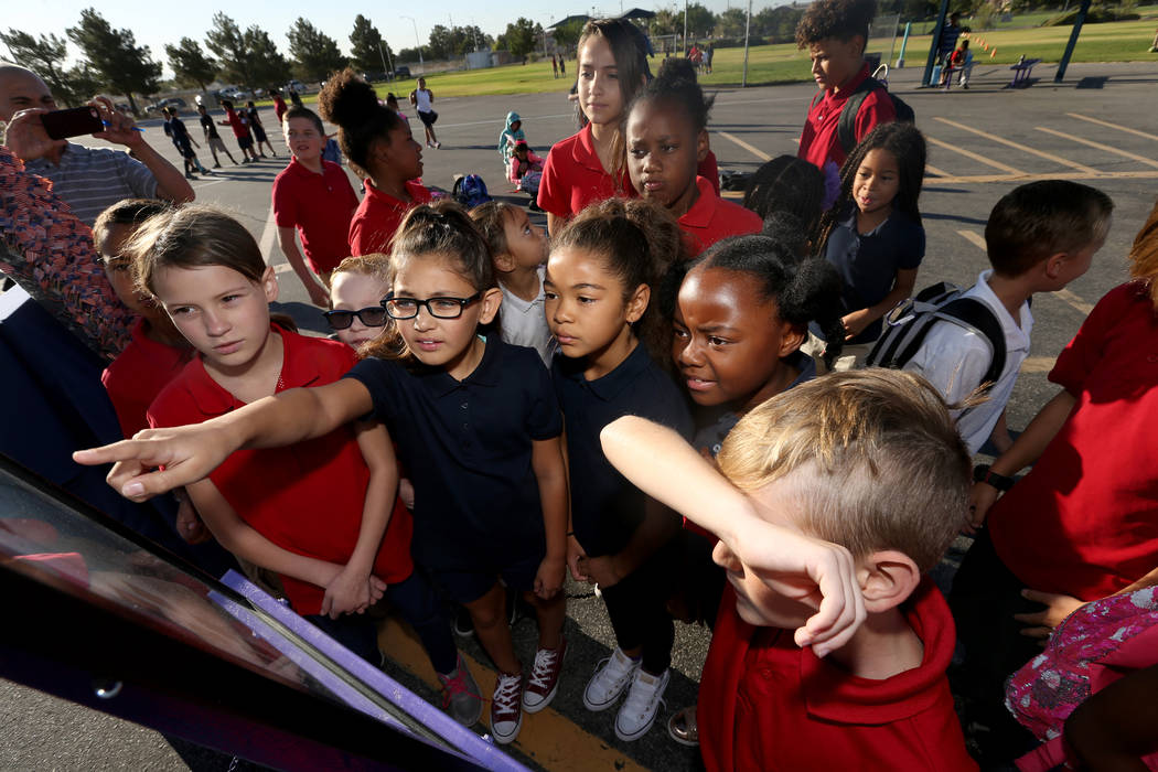 Students look at photos of people killed on 9/11 during an observance at Joseph M. Neal STEAM Academy in Las Vegas Tuesday, Sept. 11, 2018. Principal Denise Murray and her husband, a former Port A ...