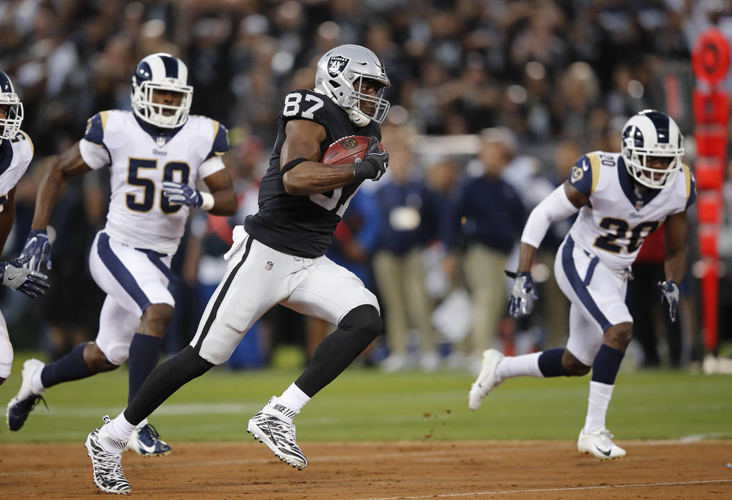 Oakland Raiders tight end Jared Cook runs with the ball past Los Angeles Rams linebacker Samson Ebukam, left, and defensive back Lamarcus Joyner (20) during the first half of an NFL football game ...