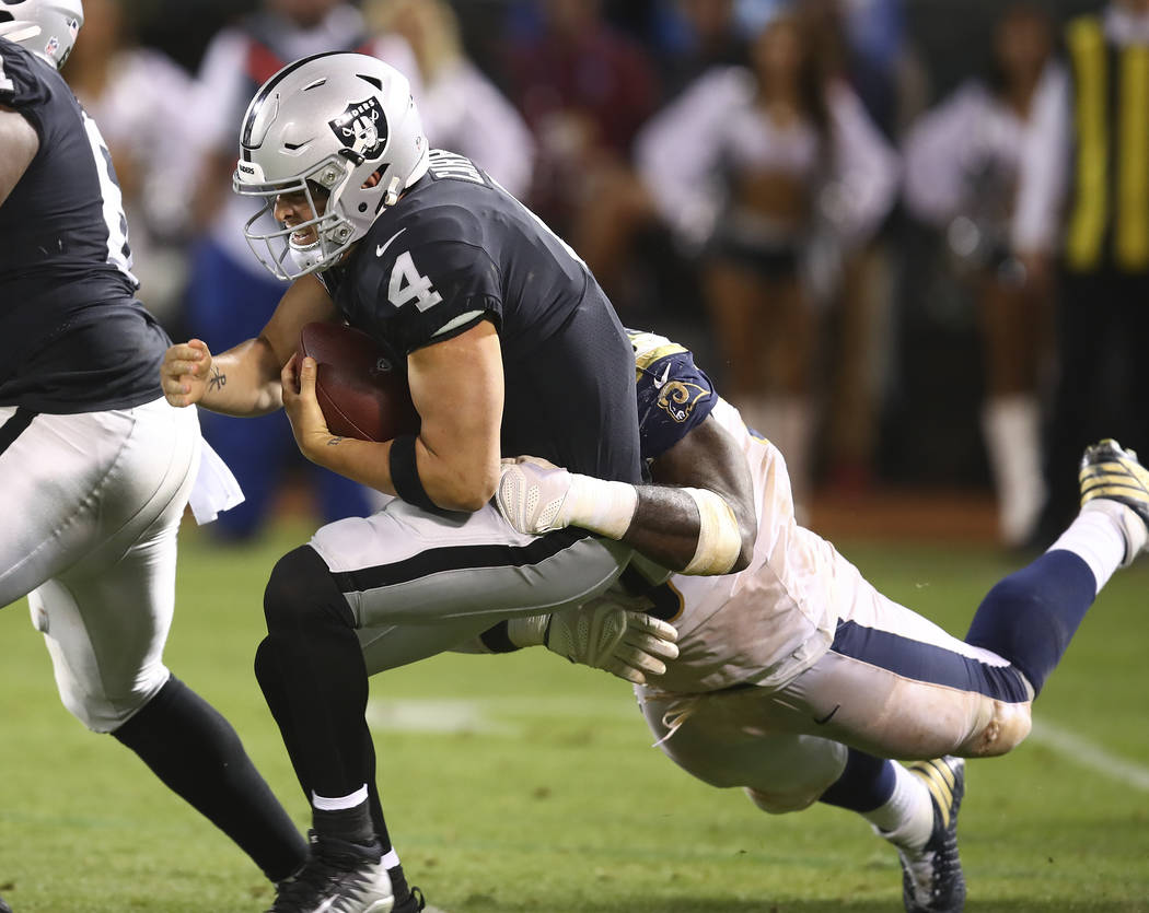 Oakland Raiders quarterback Derek Carr is sacked by Los Angeles Rams defensive tackle Michael Brockers during the second half of an NFL football game in Oakland, Calif., Monday, Sept. 10, 2018. (A ...