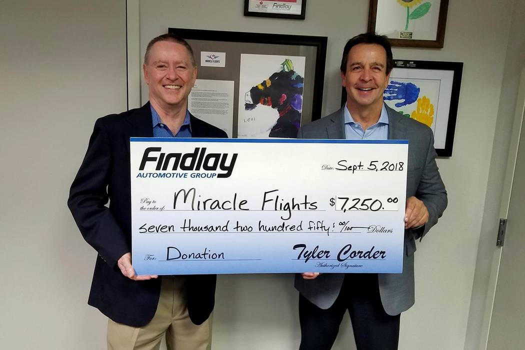Findlay Automotive Group CFO Tyler Corder, left, presents a check for $7,250 to Mark Brown, CEO for Miracle Flights. (Findlay)