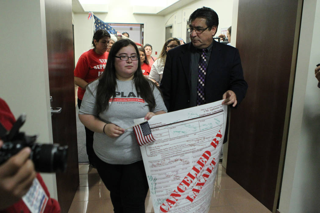 Dulce Valencia, left, with Ben Monterroso, executive director for Mi Familia Vota, deliver a letter and sign to Attorney General Adam Laxalt's office at the Grant Sawyer Building, 555 E Washington ...
