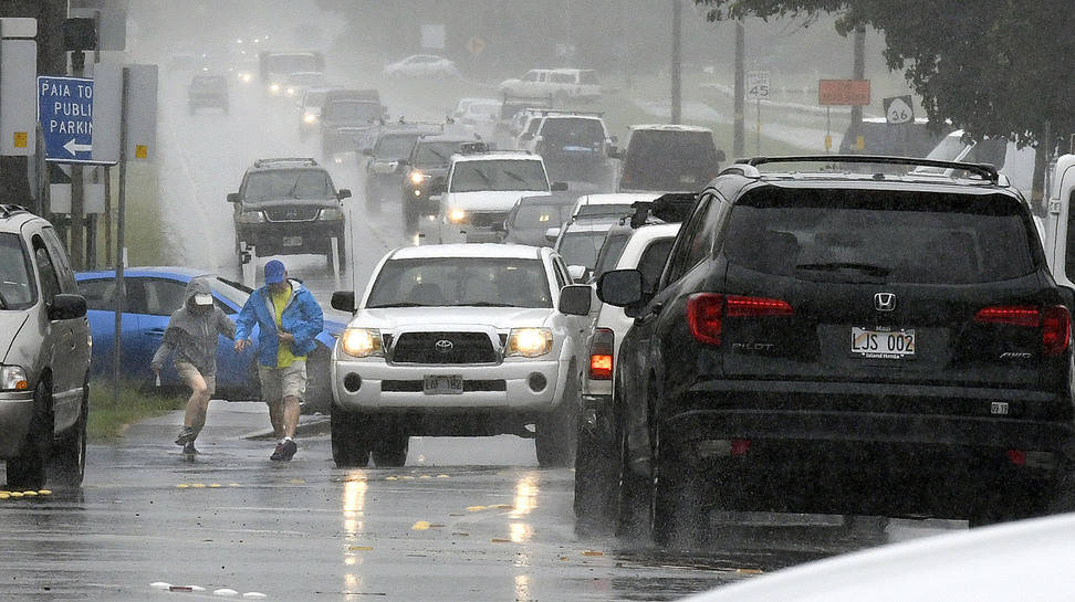 A couple walks in a rainstorm amid heavy traffic in Paia, Hawaii, on Tuesday, Sept. 11, 2018, as Tropical Storm Olivia marched closer to Maui. (Matthew Thayer/The News via AP)