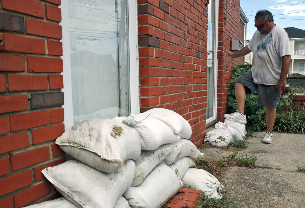 Adam Bazemore uses his foot to pack down sandbags in a doorway, Tuesday, Sept. 11, 2018, in the Willoughby Spit area of Norfolk, Va., as he makes preparations for Hurricane Florence. (AP Photo/Ale ...