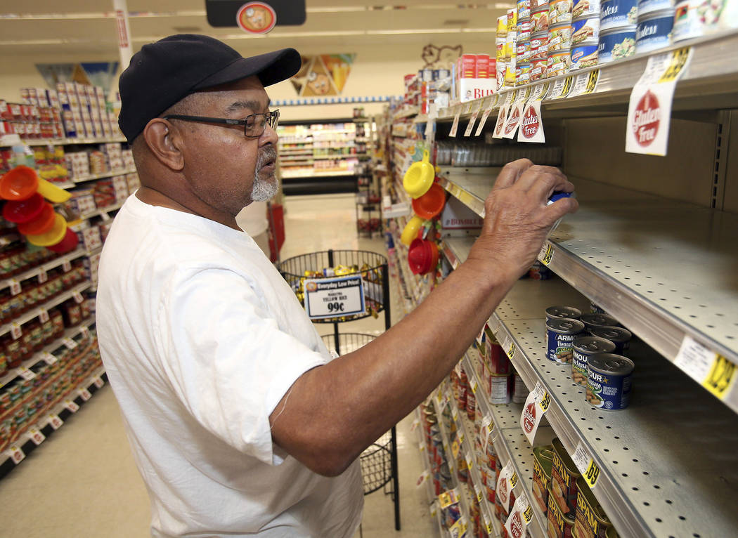 Larry Lynch selects a can of Armour Vienna Bites while grocery shopping in preparation for Hurricane Florence on Tuesday, Sept. 11, 2018, at the Piggly Wiggly store on West Thomas Street in Rocky ...