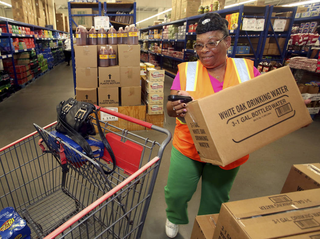 Gloria Pittman loads a box of bottled water into her grocery cart Tuesday, Sept. 11, 2018, while shopping for hurricane related supplies at Fred's Food Club in Rocky Mount, N.C. (Alan Campbell/R ...