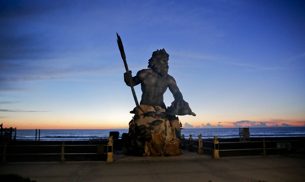 The bronze statue of Neptune stands with the sunrise behind, Wednesday, Sept. 12, 2018, in Virginia Beach, Va., as Hurricane Florence moves towards eastern shore. (AP Photo/Alex Brandon)