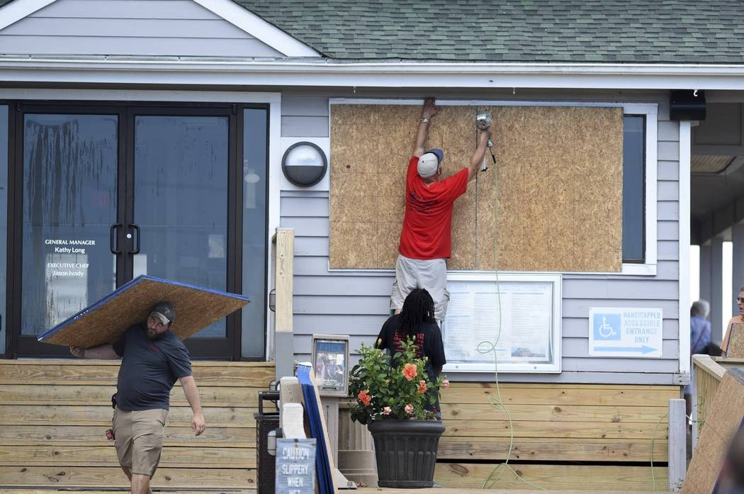 FILE- In this Tuesday, Sept. 11, 2018, photo crews board up the Oceanic restaurant in Wrightsville Beach, N.C., in preparation for Hurricane Florence. Though it's far from clear how much ec ...